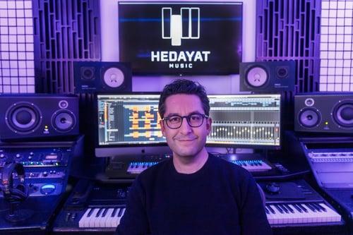 Hedayat, arrangeur/compositeur, devant du matériel de musique professionnel.