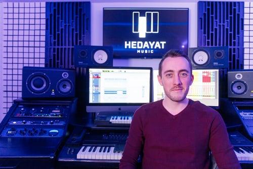 Arthur, ingénieur du son et sound designer, devant du matériel de musique professionnel.